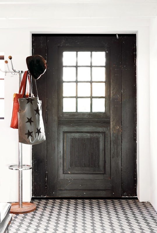 A black antique door and rough marble mosaic tile floor in a rustic entryway