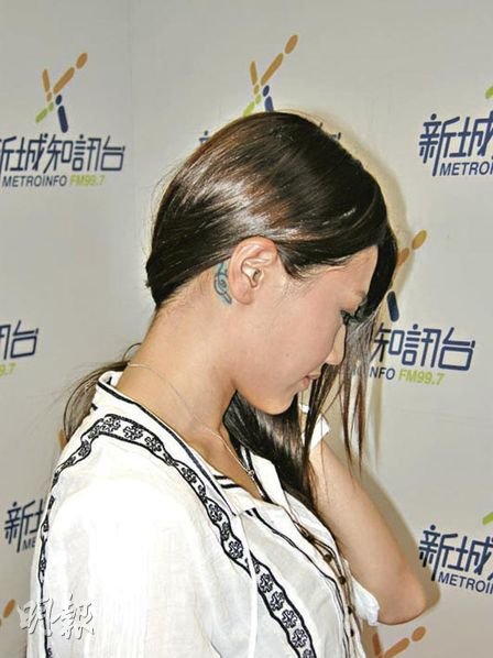 Chrissie Chau shows off her behind-the-ear tattoo while promoting a theme