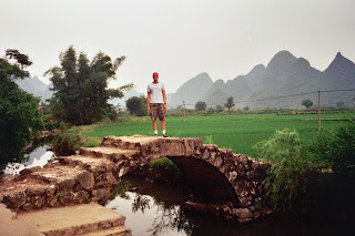 Standing on a bridge amid rice paddies watching a man gut a chicken in the canal below me
