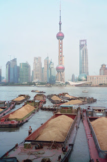 A traffic jam of barges against the skyline of Shanghai