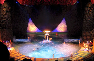 Cirque du Soleil performers diving into the pool using swinging platforms.