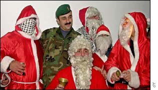 Palestinian men, dressed as Santa Claus, surround a guard