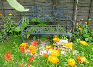 Garden bench with pot marigolds and red poppies in front.