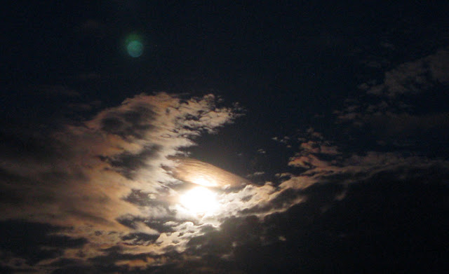 Full moon in clouds on 24th July 2010, with green unidentified object in sky.