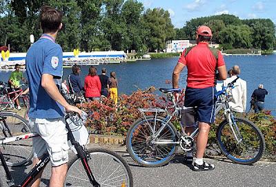 Dwóch rowerzystów ogląda start wioślarzy