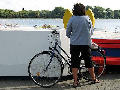 Rowerzystka obserwuje start wioślarzy