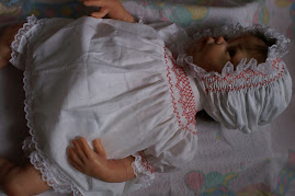 White cotton with red smocking.