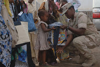 Navy Senior Chief Legalman Alicia Barnes hands a book bag containing school supplies, flip flops, soap, shampoo and treats to a young girl at The Center for the Protection of Women and Children, the largest orphanage in Djibouti. (U.S. Navy photo)
