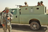 Spc. Donald Hock, the senior medic for the Combat Operating Base Speicher Security Detachment, provides security April 3 alongside a truck of Iraqi army soldiers tasked with guarding oil lines near Tikrit. On the truck is a painted logo of an oil well. U.S. Army photo.