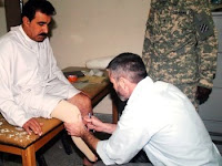 Chris Cummings, a prosthetist in the IA surgeon general's office prosthetics clinic in Baghdad, runs some tests on 1st Lt. Mohy Ali's limb during an initial visit on April 21. Mohy, an IA soldier, lost his foot during an IED attack on Jan. 10 while on a joint mission with Coalition forces. (U.S. Army photo by Sgt. 1st Class Tami Hillis)