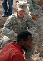 Spc. Samuel Rasmussen, Joint Combat Search and Rescue security team rifleman, Bravo Battery, 2nd Battalion, 18th Field Artillery Regiment, renders first aid to an injured civilian at the scene of a vehicle accident in Djibouti June 24, 2008. (RELEASED) Photo by Air Force Tech Sgt. Katherine Garcia.