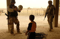 A Iraqi soldier and an American Soldier play with a child as his family speaks with the Iraqi Army and Coalition troops about activity in their area July 29 in the al Jazeera desert near Balad, Iraq. (Army photo by Staff Sgt. Micky Bazaldua)