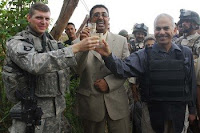 Capt. Benjamin Neasse (from left) celebrates raises a toast with a local contractor and Dean Michael, a bilingual bicultural adviser, to the completion of a water distribution system in the Muhmudiyah Qada Nov. 4, 2008.