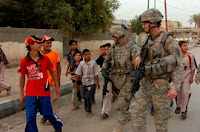 Staff Sergeant Brian Doty (left), of Orange, Va. and Cpl. Sam Weaver, of Fayetteville, N.C., both with Company B, 13th Psychological Operations Battalion, are accompanied by local children while on a foot patrol in the city of Suwayrah in northern Wasit province. Photo by Sgt. David Turner.