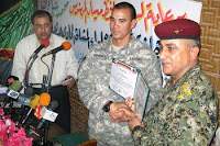 Army Capt. Steven Kendall presents a partnership certificate to Iraqi Army Lt. Col. Hillal at a ceremony to mark what Iraqis are calling National Sovereignty Day in Majaar Al Kabir, Iraq, June 30, 2009. Following the ceremony, Kendall's unit vacated its combat outpost at a defunct sugar factory while Iraqi soldiers moved in.