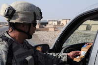 Staff Sgt. Paul Cruz checks a driver's identification at a checkpoint outside Baghdad. Since U.S. troops pulled out if Iraqi cities, attacks in the Iraqi capital have been on the decline.