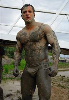 Homens lambuzados de lama