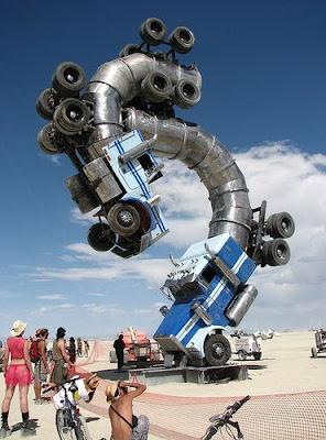 Escultura feita com caminhões simula luta entre escorpiões.