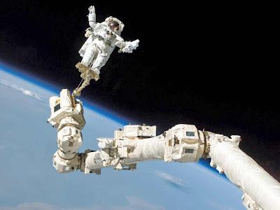 Astronauta  na ponta do braço mecânico da nave espacial - plano de fundo