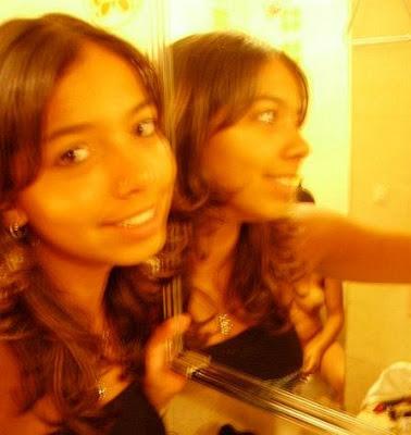 Menina de preto fotografa no espelho, sem querer a mãe.