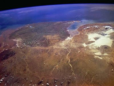Imagem de Porção de continente e de oceano delimitados ao fundo pelo espaço.