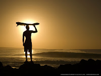 Surfista observa as ondas ao por do sol.