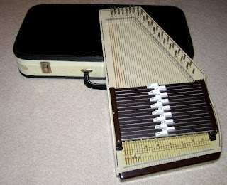 An autoharp. The image was taken from http://www.karlosthejackal.com/drowsy/gallery/