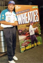 Denny Brauer posing with a poster of himself on a box of Wheaties. Image taken from http://www.bassfan.com/news_article.asp?ID=65