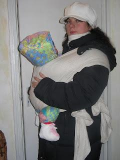 Szöveg: Nagynéninek is muszáj volt kipróbálnia. Kép: Téli ruhűkba beöltözött nagynénin (fehér esővédős sapka, fehér sál, fekete hosszú kabát) a már ismert kendőbe tekerve füsrendbe bújtatott gyermekecske.