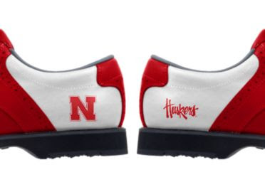 University of Nebraska golf shoes with a red letter N on one shoe and the word Huskers written on the other above black soles and cleats.