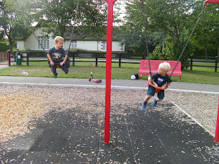 swinging high. Baby bucket swings in the park