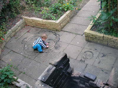 pavement artist drawing faces in charcoal on the patio