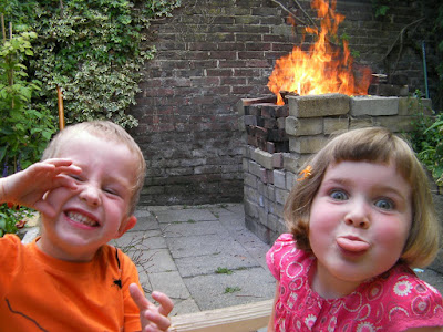 fire and abuse. 2 happy children pulling faces and a bonfire