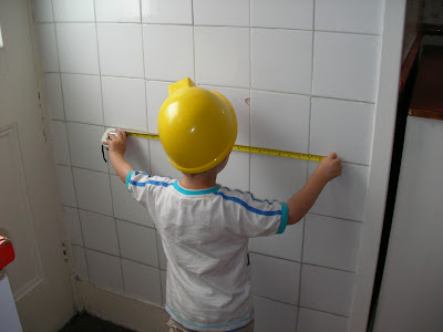 builder measuring tiles with tape measure in bob the builder hard hat