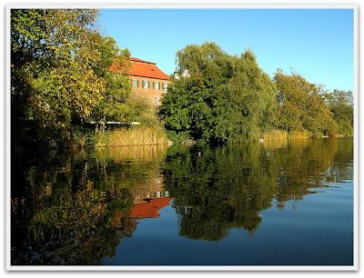 Ett hus som speglas i vattnet.