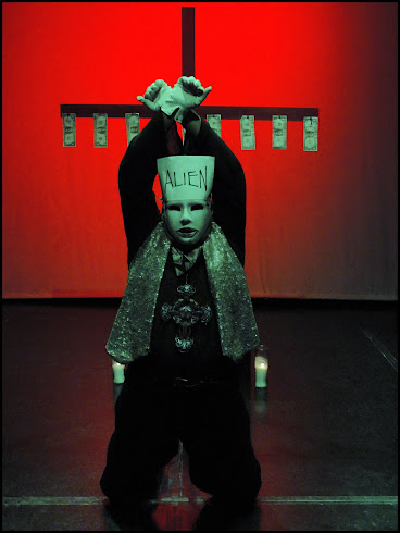 José Torres-Tama as ALIEN character Kneeling Before the Cross of Dollars.