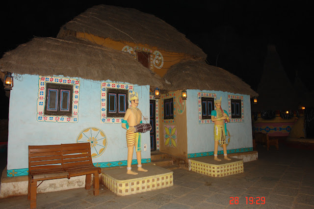 Photo of Hut with statues of 2 musicians outside in the village of Chokhi Dhani