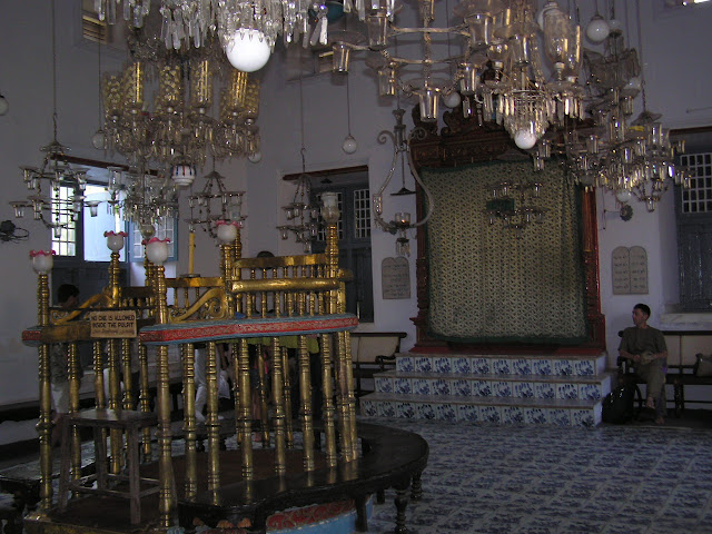 An inside view of the Jewish synagogue in Cochin (Paradesi Synagogue) in Kerala, India, with a person sitting near the pulpit