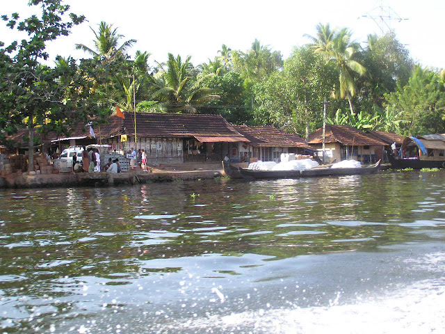 People on the side of the canal with a lot of greenery in the town of Alleppey in Kerala, India
