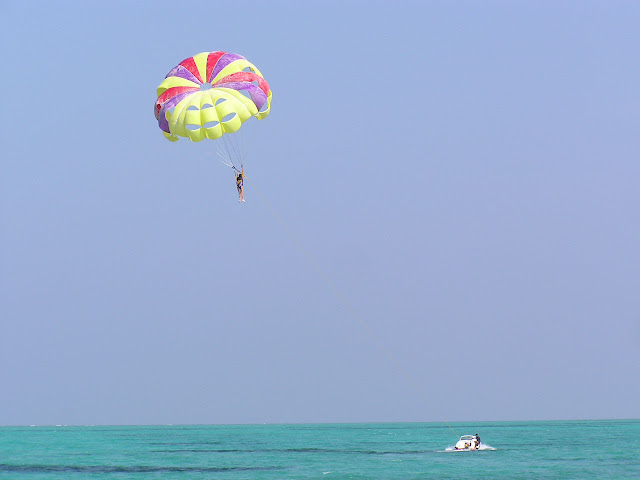 Floating in a parasail over the beautiful green water, pulled by a boat