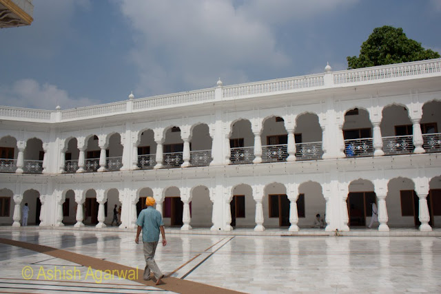 A Sikh walking towards the set of buildings just behind the Akal Takht in the Golden Temple in Amritsar