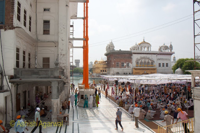 View of Nishaan Sahib (flagstaffs) along with poeple congreagating and view of the sarovar in the Golden Temple