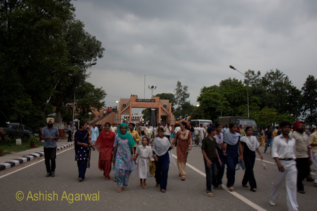 People walking away from the border for the flag lowering ceremony at the Wagah Border between India and Pakistan