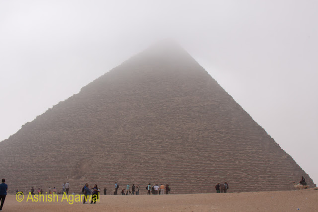 Cairo Pyramids - People standing at the base of the huge Great Pyramid of Cheops