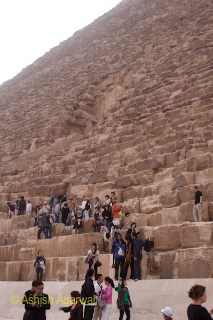Cairo Pyramids - a portrait image of people at the foot of the Great Pyramid in Giza