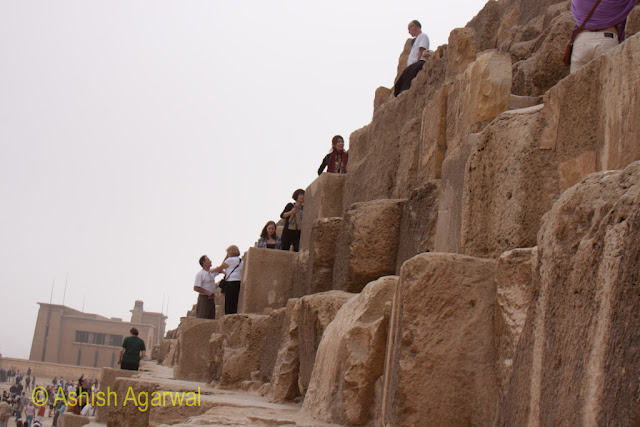 Cairo Pyramids - People climbing the stone steps of the Pyramid in Giza