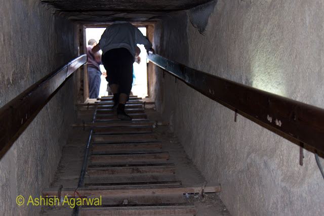 Cairo Pyramids - Tourist climbing out of the burial chamber of the structure next to the Great Pyramid of Cheops