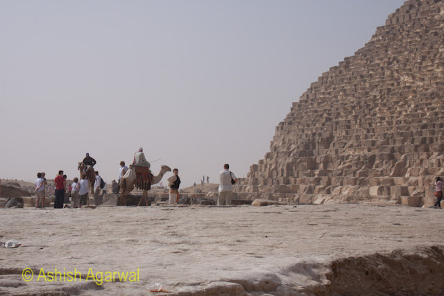 Cairo Pyramids - View of people and camel at the base of the Great Pyramid