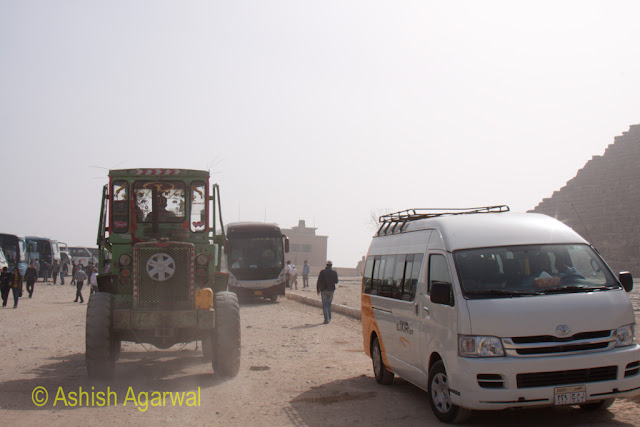 Cairo Pyramids - A heavy vehicle and a tourist cab just on the side of the Great Pyramid