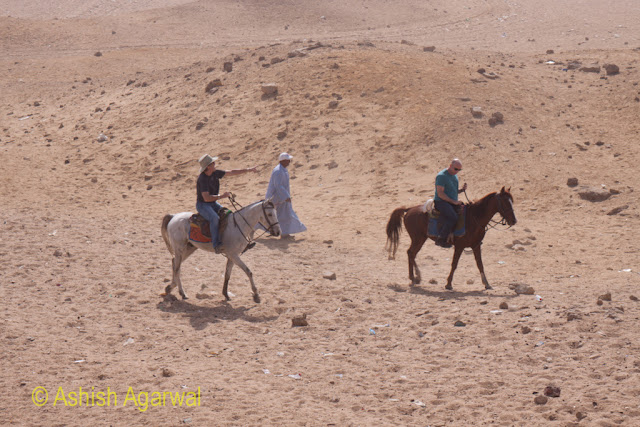 Giza Panorama Point - Horses and tourists on the sand of Giza near the Pyramids